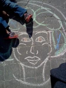 Sidewalk chalk drawing with a little kid sitting on it.